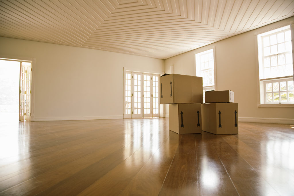 Moving services NJ represented by some moving boxes in an empty room