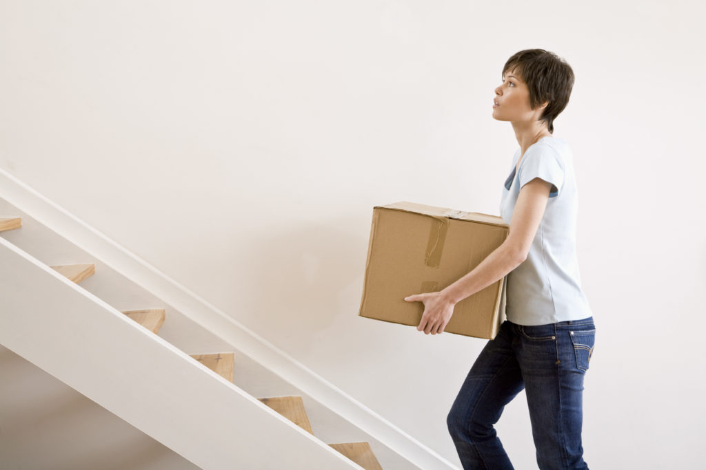 woman carrying box upstairs