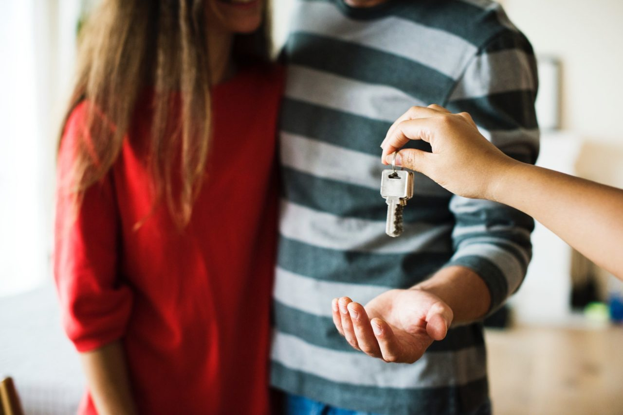 someone giving keys to a couple