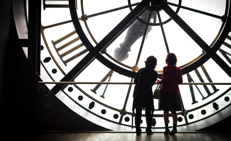 silhouettes in front of a clock