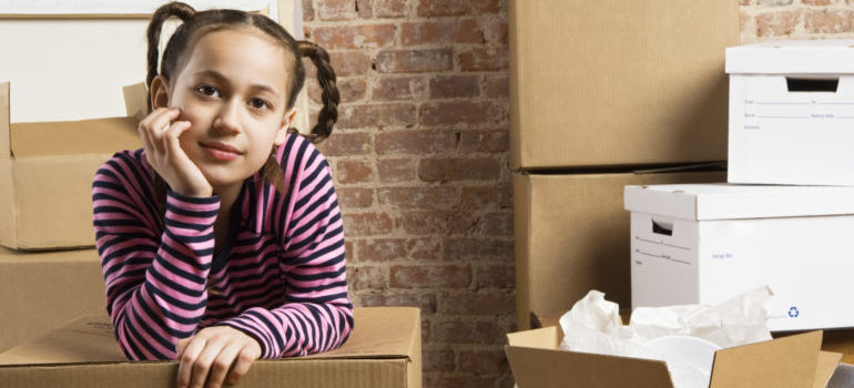 a little girl moving into a new home, leaning onto a moving box