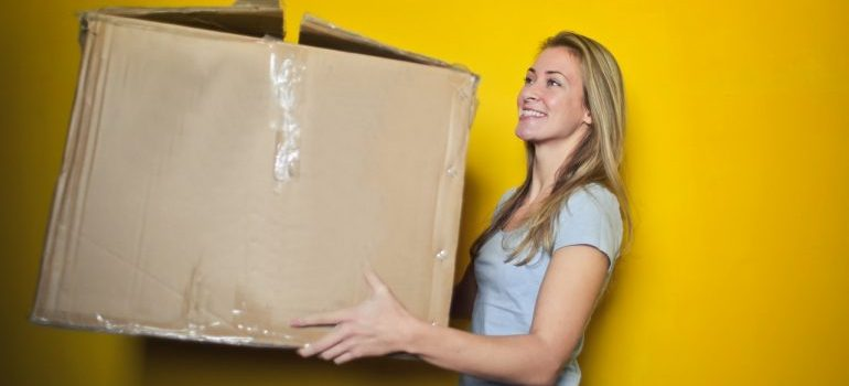 label moving boxes - woman carrying a box