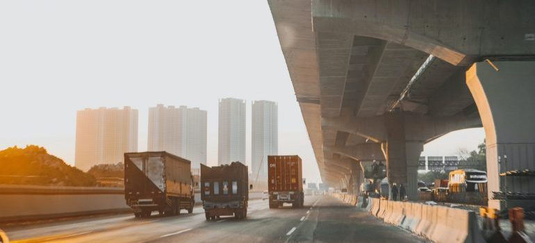 Trucks on the road with cityscape in the background