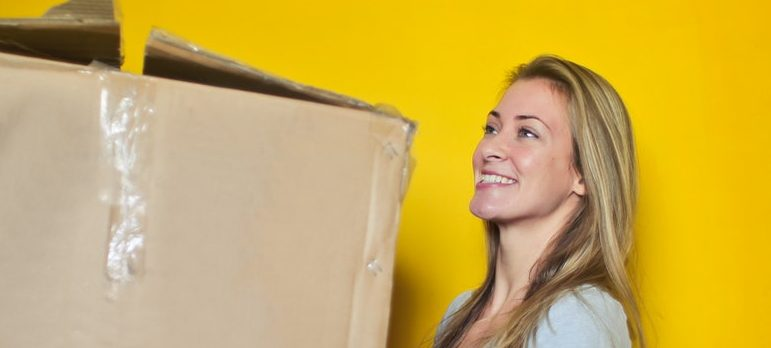 Girl preparing for short distance moving with a box.