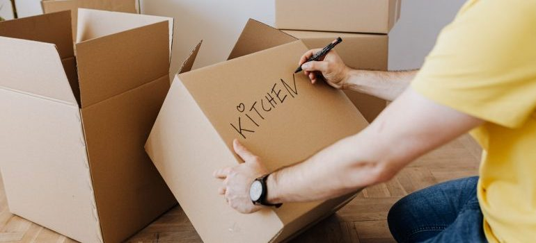 A man labeling a cardboard box with a marker.