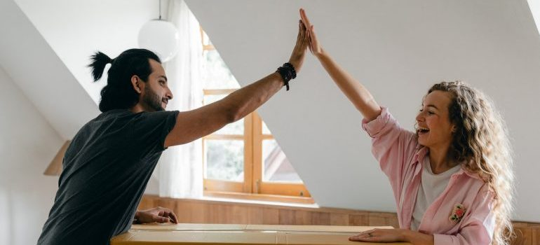 Happy couple high-fiving after a successful move with Piscataway Township movers.