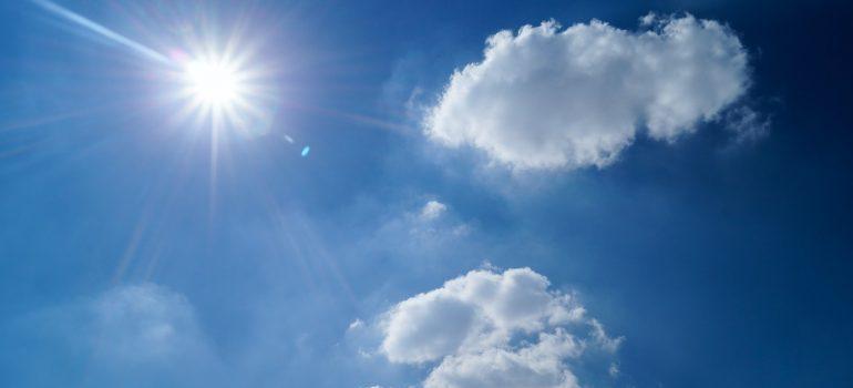 A blue sky, sun and clouds.