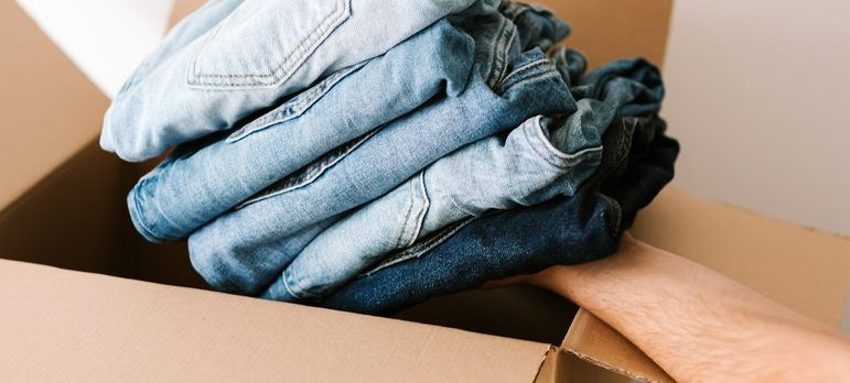 A person packing clothe for moving.