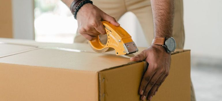 A man sealing a cardboard box.