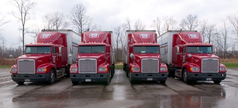 Four red, parked trucks used by Alexandria Township movers.
