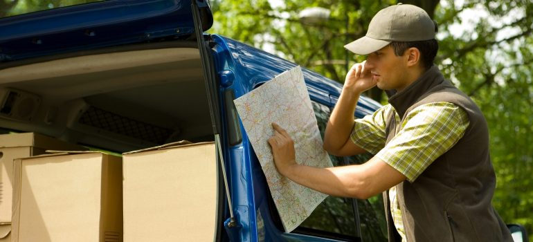 A courier looking at a map while his van is filled with boxes.