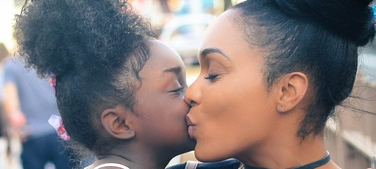 Mother kissing a daughter