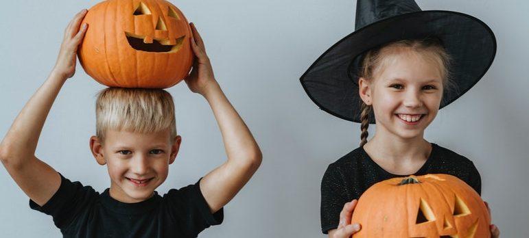 Two kids holding Halloween pumpkins.
