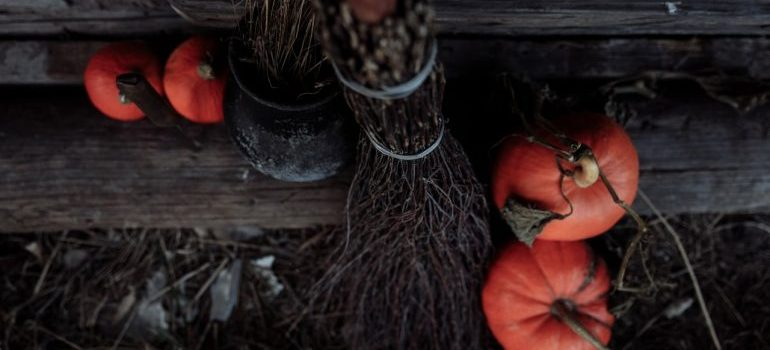 A broom and some pumpkins.