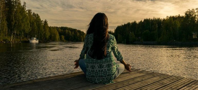 A woman meditating in order to relax.