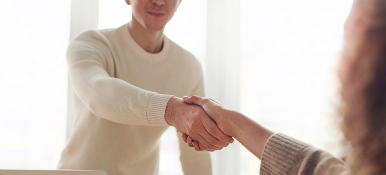 A man shaking the hand of a woman.