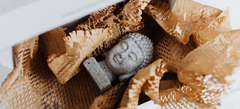 person packing buddha statue in a box