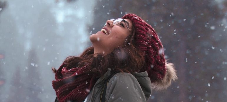 A woman looking at the sky while snowing