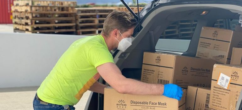 A man in a bright green t shirt loading a van while wearing blue gloves and a mask for protection.