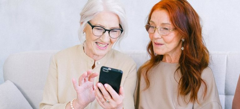 Two senior women looking at a phone.