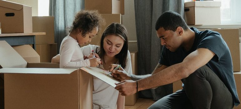 A child in a box helping parents pack