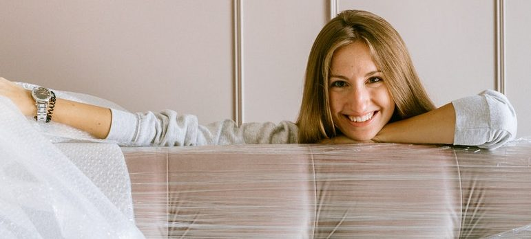 A woman standing next to a wrapped sofa