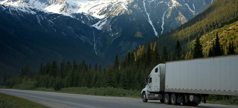image of a truck on road with mountains in the background