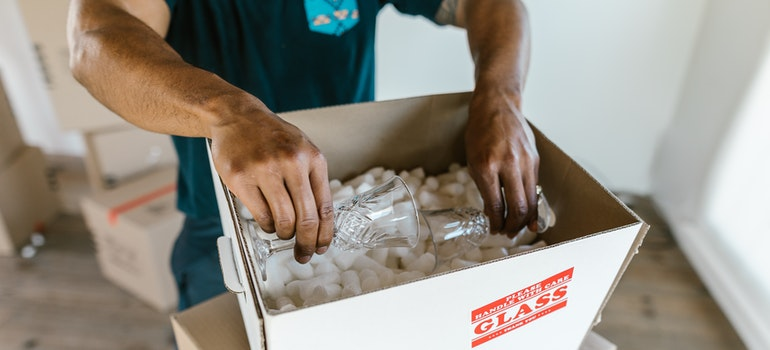 person packing glasses into a box