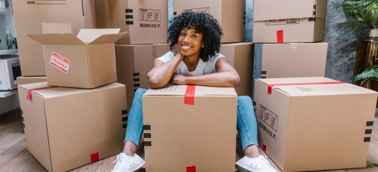 Woman sitting next to moving boxes
