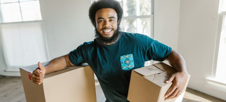 Mover smiling and carrying boxes