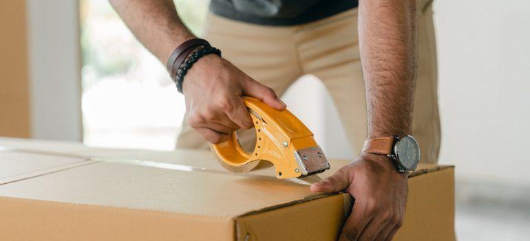 a man sealing a cardboard box