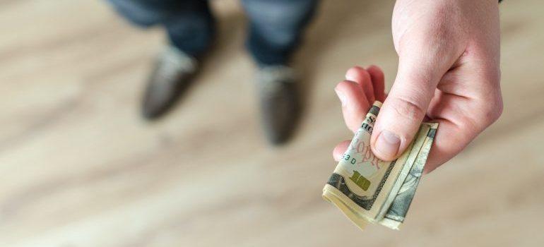 A man handing over dollar bills