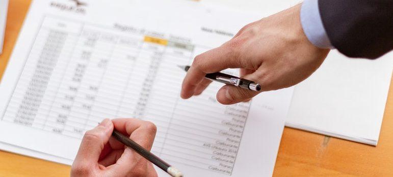 Two people disusing paperwork