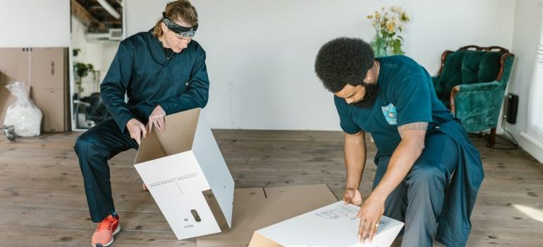 two movers setting up boxes