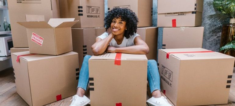 Woman sitting in front of packed boxes