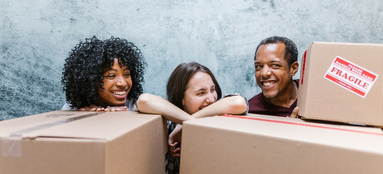 three happy people behind moving boxes
