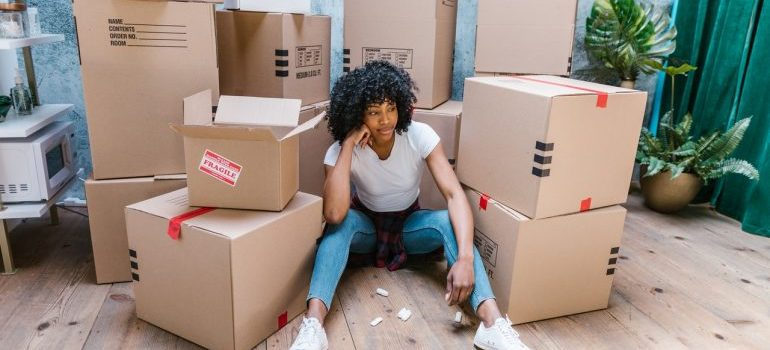 A worried woman surrounded by boxes