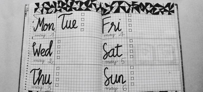 Black and white weekly planner on gray surface