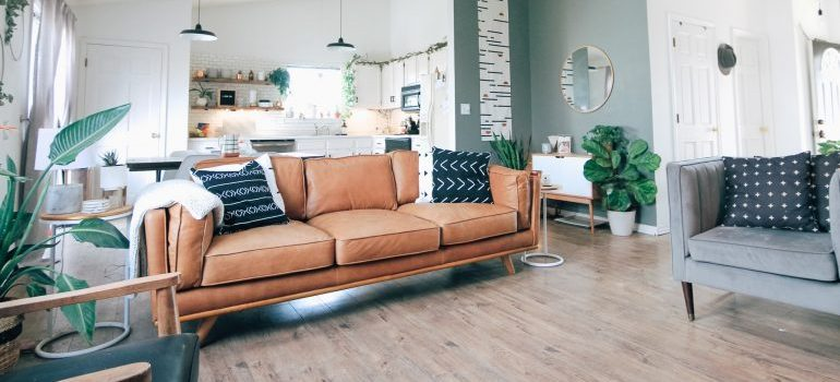 A living room with a wooden floor, sofa, and two armchairs