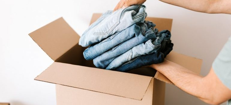 Person putting folded jeans in a moving box