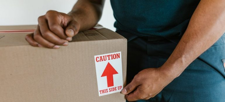 a man working for Prospect Park movers holding a cardboard box with a label on it